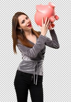 Piękna młoda dziewczyna trzyma piggybank