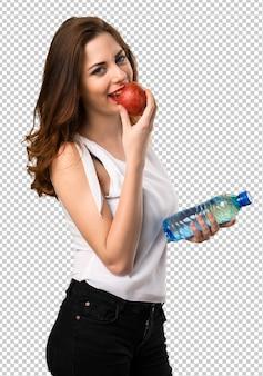 Piękna młoda dziewczyna z jabłkiem i wodą