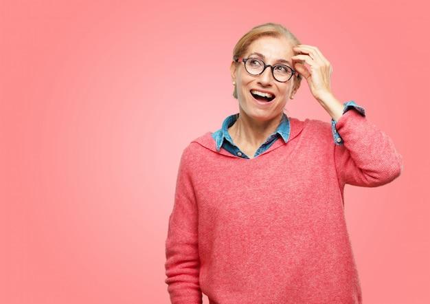 Piękna starsza kobieta szczęśliwie realizuje pewne dobre i zaskakujące wiadomości lub o świetny pomysł