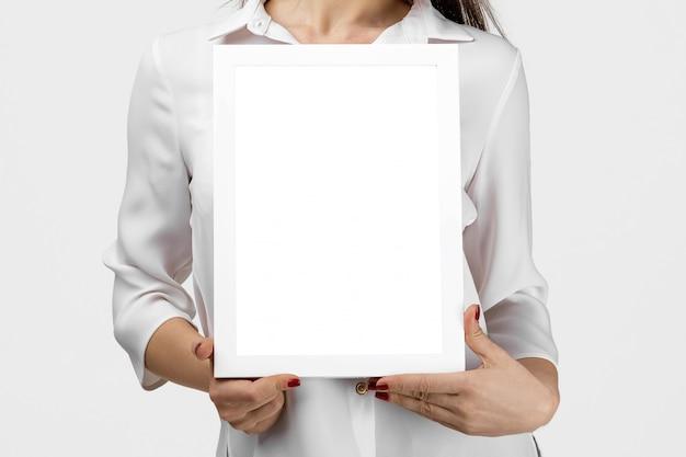Piękna uśmiechnięta kobieta trzyma puste miejsce deskę