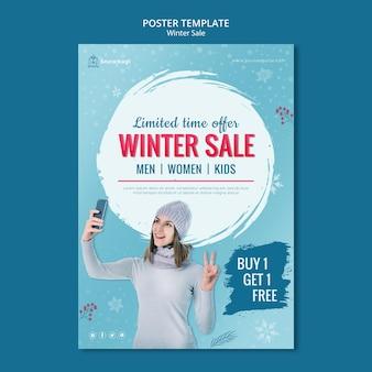 Pionowy plakat zimowej wyprzedaży z kobietą i płatkami śniegu