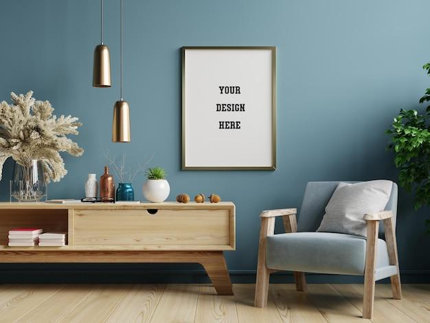 Plakatowa makieta z pionową ramą na niebieskiej ścianie we wnętrzu salonu z niebieskim aksamitnym fotelem