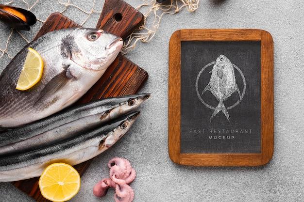 Płaski układ owoców morza z makietą na tablicy