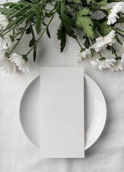 Płaski układ stołu z makietą wiosennego menu na talerzu i mnóstwem kwiatów