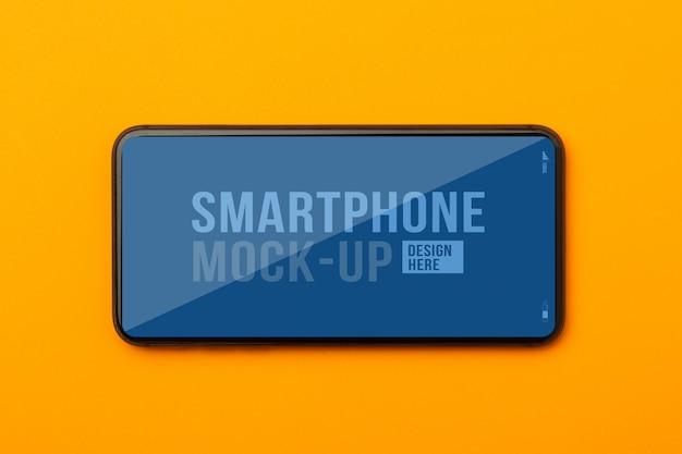 Płaski układ, widok z góry pomarańczowego biurka biurka z szablonem makieta smartfona do projektowania.