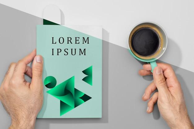 Płaskie ręce trzymające makietę książki i kawę