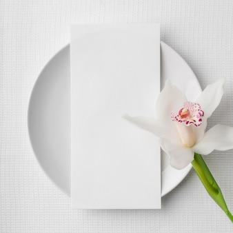 Płaskie ukształtowanie makiety menu wiosennego na talerzu z kwiatem