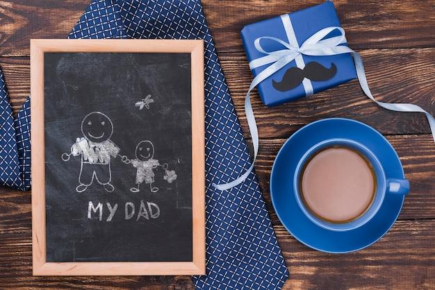 Płaskie ukształtowanie ramy z krawatem i prezentem na dzień ojca