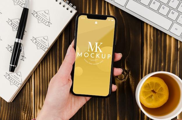 Płasko świeckich dłoni trzymającej smartfona makiety z herbatą na biurku