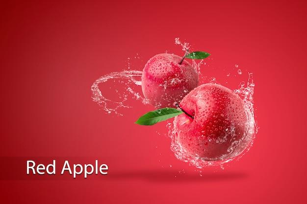 Plusk wody na świeże czerwone jabłko na czerwonym tle.