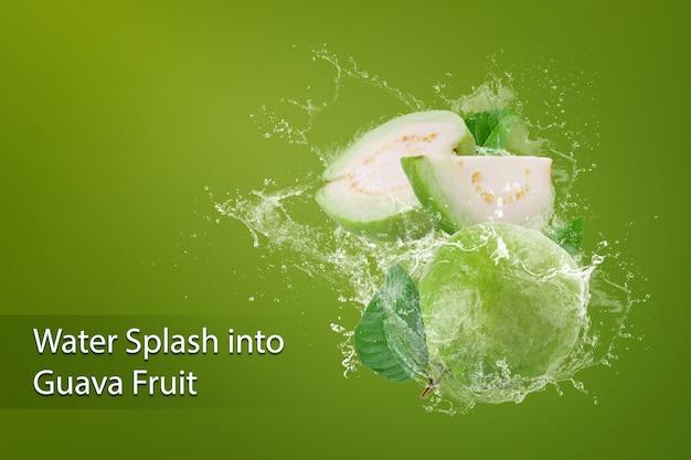 Plusk wody na zielonych owocach guawy nad zielenią
