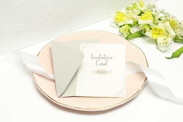 Pocztówka na różowym talerzu z białą wstążką, szarą kopertą i białymi kwiatami
