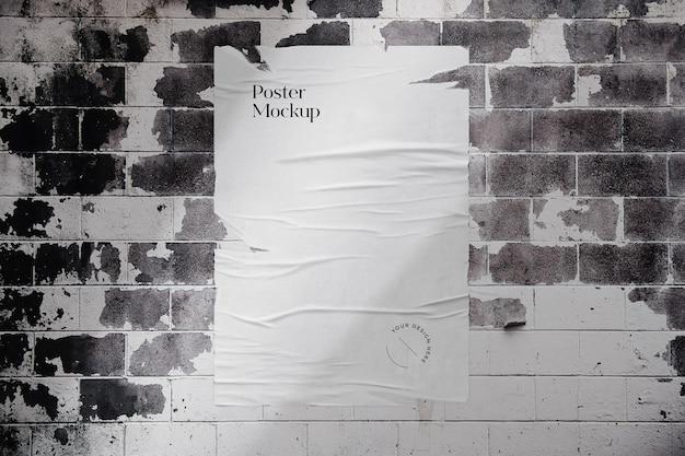 Podarta makieta plakatu na ścianie z cegły
