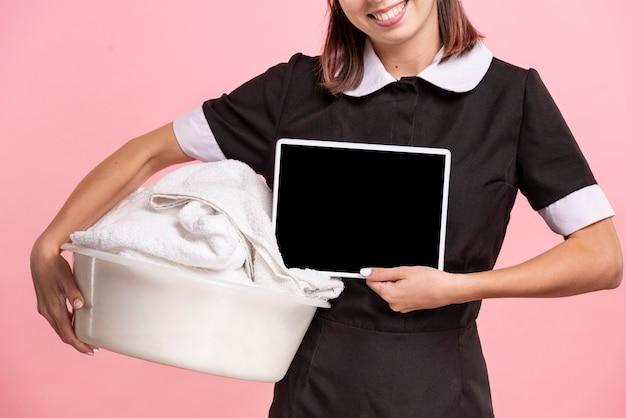 Pokojówka z ręcznikiem trzymając makietę tabletki