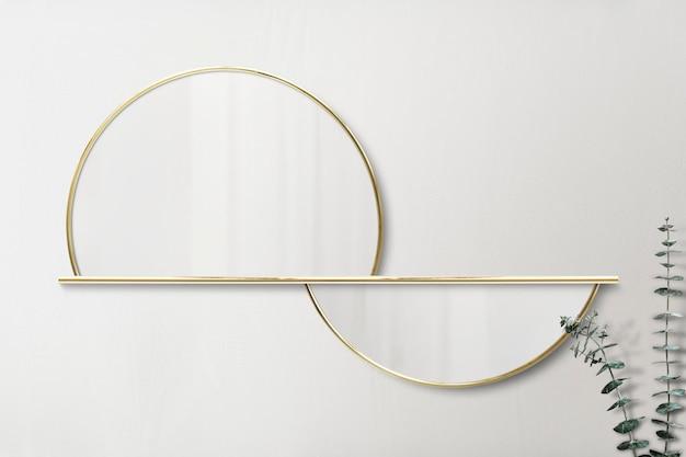 Półokrągłe lustro w złotej oprawie na beżowej makiecie ściennej
