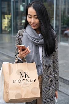 Połowa strzału kobiety trzymającej torby na zakupy i telefon