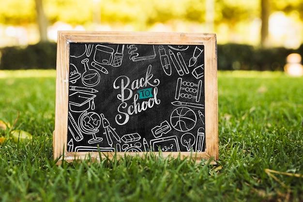 Popiera szkoły blackboard na trawy makiecie
