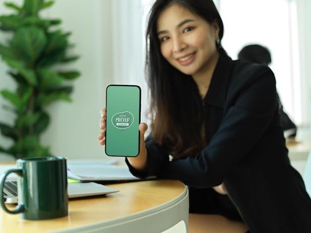 Portret bizneswoman trzyma smartphone i pokazuje ekran makiety