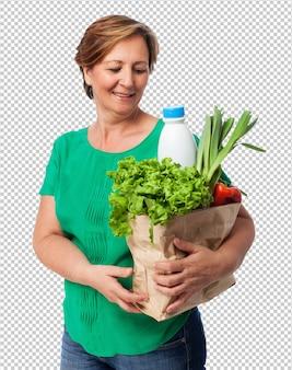 Portret dojrzała kobieta niesie torba na zakupy z jedzeniem
