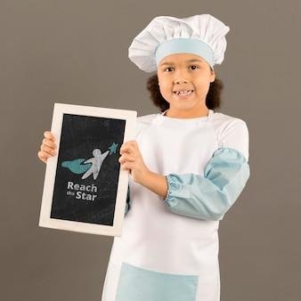 Portret młoda dziewczyna pozuje jako szef kuchni