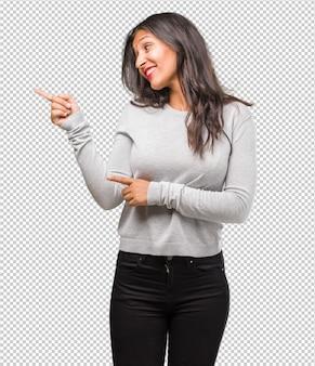 Portret młoda indyjska kobieta wskazuje z boku, uśmiecha się zdziwiony przedstawiający coś, naturalny i przypadkowy