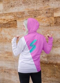 Portret młoda kobieta wskazuje przy hoodie
