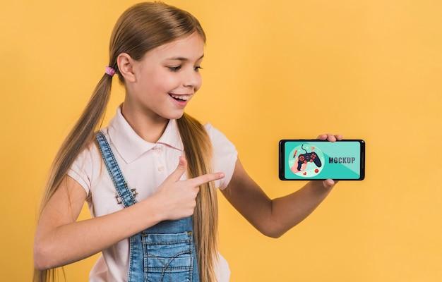 Portret młodej dziewczyny trzymając telefon komórkowy z makiety