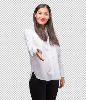 Portret młodej kobiety indyjskiej, która wyciąga rękę, aby kogoś przywitać lub gestem pomaga, szczęśliwa i podekscytowana