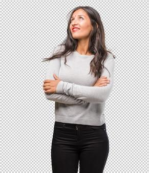 Portret młodej kobiety indyjskiej patrząc w górę, myśląc o czymś zabawnym i mając pomysł