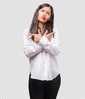 Portret młodej kobiety indyjskiej zdezorientowany i wątpliwy, zdecyduj między dwiema opcjami