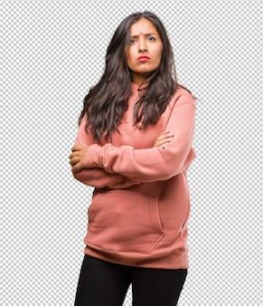 Portret sprawności fizycznej młoda indyjska kobieta krzyżuje jego ręki, poważny i nakładający, czuje się pewny i pokazuje siłę