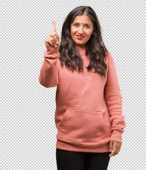Portret sprawności fizycznej młoda indyjska kobieta pokazuje liczbę jeden, symbol liczenie, pojęcie matematyka, ufny i rozochocony