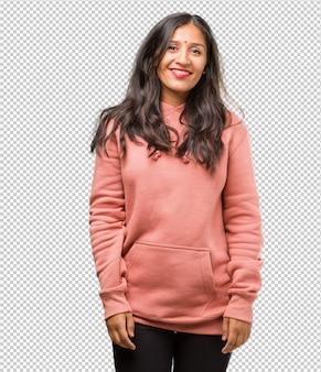 Portret sprawności fizycznej młoda indyjska kobieta rozochocona z wielkim uśmiechem, ufna, życzliwa i szczera, wyrażająca pozytywność i sukces