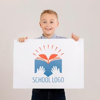 Portret szczęśliwy chłopiec trzyma znak makiety