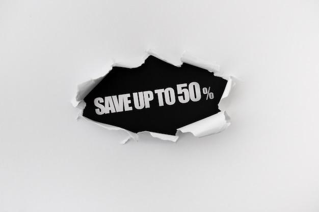 Poszarpana dziura w białej ścianie papieru na czarnym tle