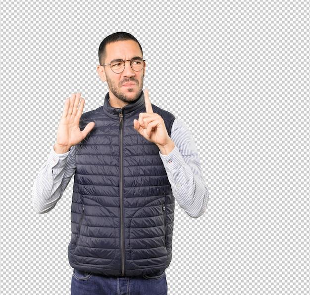 Poważny młody człowiek prosi o ciszę, wskazując palcem