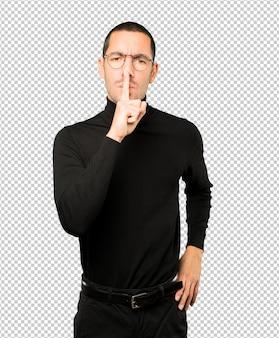 Poważny młody człowiek proszący o ciszę, gestykulując palcem