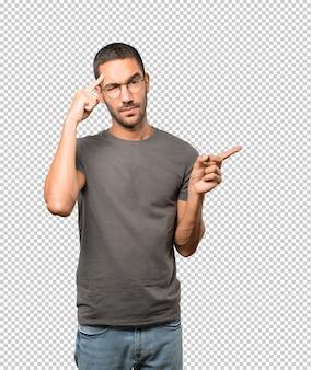 Poważny młody człowiek robi gestowi koncentracja