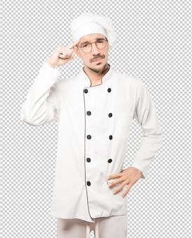 Poważny młody kucharz robi gest koncentracji