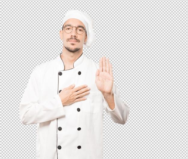 Poważny młody szef kuchni z gestem przysięgi