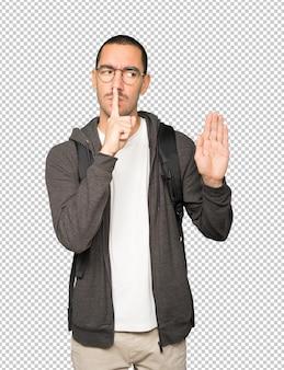 Poważny student proszący o ciszę, gestykulując palcem