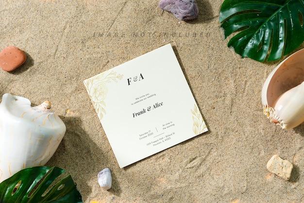 Powitanie makiety karty na piaszczystej plaży z muszlami i liśćmi.