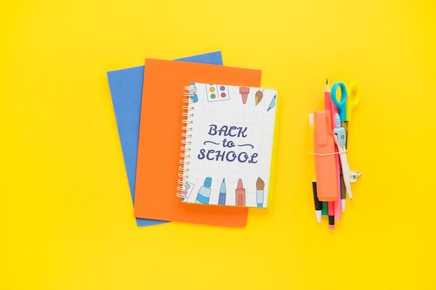 Powrót do szkoły makieta z okładką notebooka na papierach