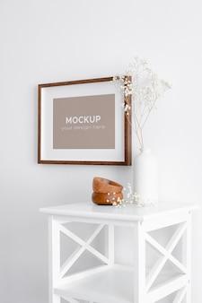 Pozioma makieta ramki do zdjęć lub grafiki na białej ścianie z suchą rośliną gipsówki w wazonie