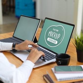 Pracownik biurowy za pomocą makiety laptopa, tabletu i materiałów eksploatacyjnych