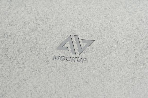 Projekt logo makiety litery na minimalistycznym szarym papierze