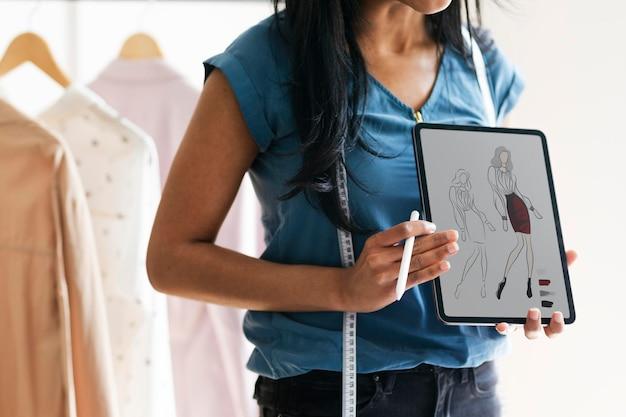 Projektant mody trzymający tablet z rysunkiem projektowym