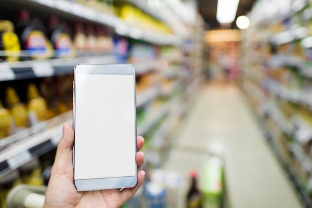 Przeglądając smartfon w supermarkecie