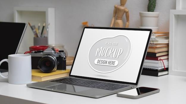 Przycięte ujęcie makiety laptopa na stole roboczym ze smartfonem, aparatem, książkami, papeterią i materiałami eksploatacyjnymi