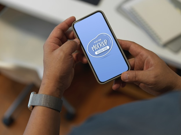 Przycięte ujęcie mężczyzny za pomocą makiety smartfona stojącego przy stole roboczym w biurze